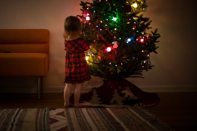 A young girl facing a decorated christmas tree
